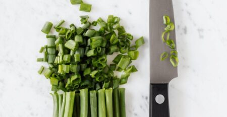 Three-riveted knife cutting fresh green onion