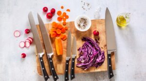set of new professional kitchen knives on a wooden cutting board and vegetables